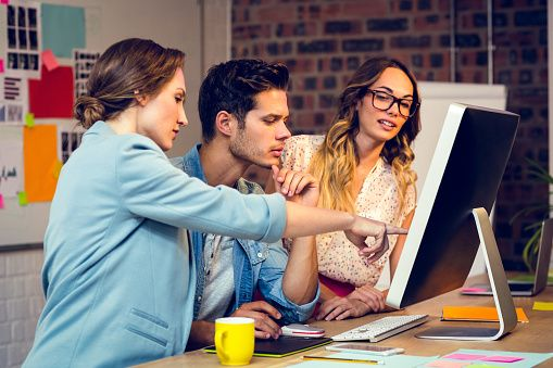 Graphic designers discussing over computer in office